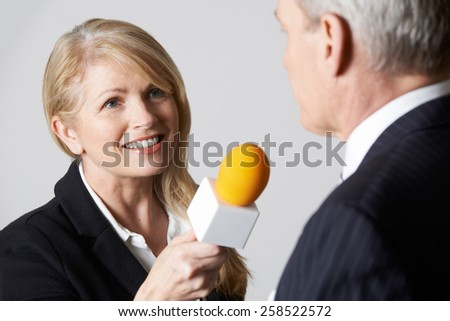 Female Journalist With Microphone Interviewing Businessman - stock photo