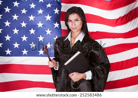 Female Judge With A Law Book And A Wooden Gavel Standing In Front Of American Flag - stock photo