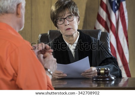 Female judge with older male  prisoner in a courtroom - stock photo