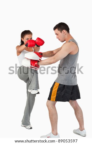 Female kick boxer practicing her knee technique against a white background - stock photo