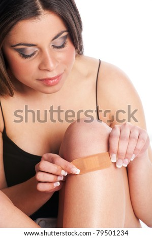 Female, Knee Injury with elastic plaster being applied. - stock photo