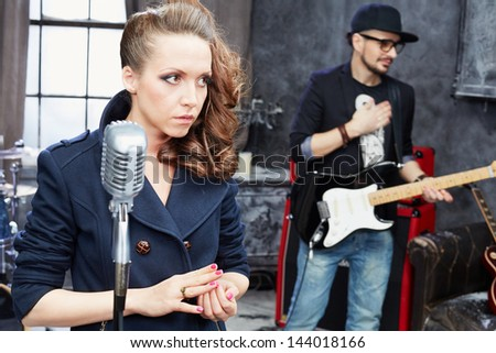 Female lead vocal and guitarist in studio - stock photo