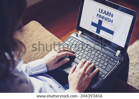 Female learning finnish at home with a laptop computer at home. - stock photo