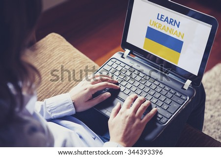 Female learning ukranian at home with a laptop computer at home. - stock photo