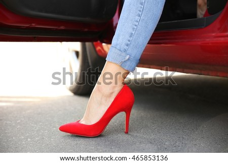 Female leg in red shoe from opened car door