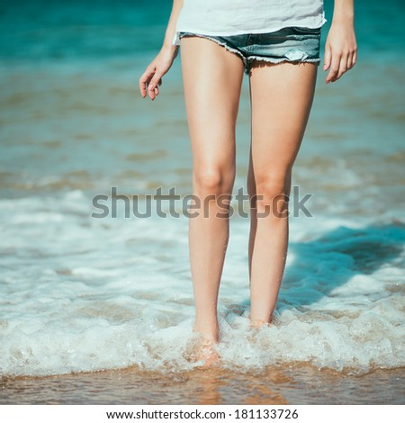 Female leg walking on the beach in the ocean. Photo in color style instagram filters  - stock photo