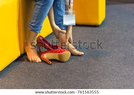Female legs are wearing fashion shoes of high heels as painful toes,Relax woman after work on the couch High heels shoe feet pain  in exhibition hall