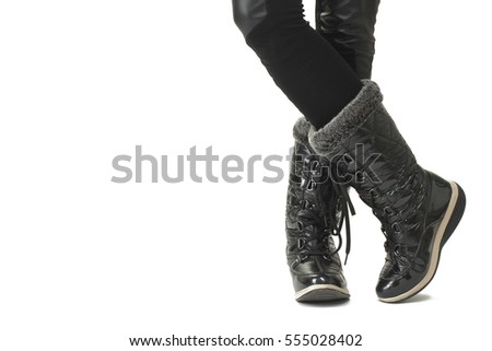 Female legs in black winter boots, isolated on white background.