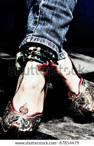 female legs in blue jeans and oriental shoes - stock photo