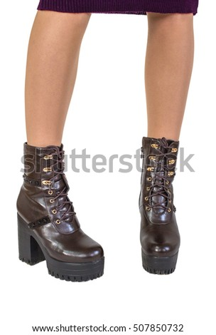 Female legs in brown boots on a big heel. Boots on white background
