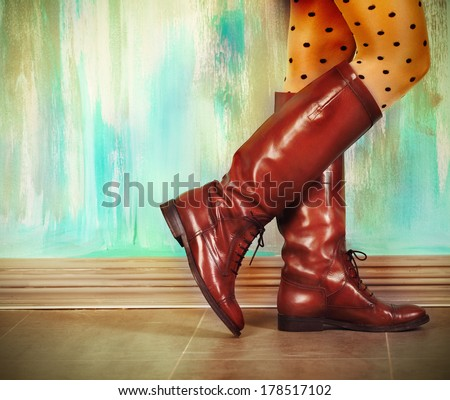 Female legs in high brown leather boots near the wall - stock photo