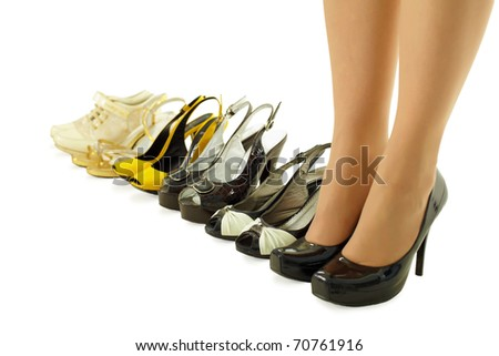 female legs in high heels and a number of different summer shoes - stock photo