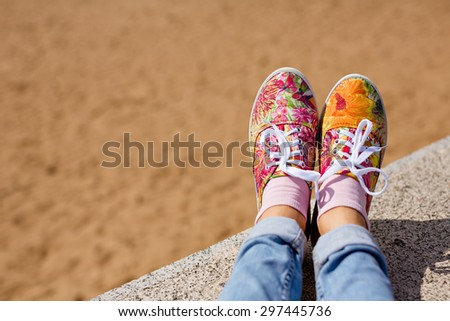 female legs in jeans and a bright floral sneakers in the background of the sand in the summer - stock photo