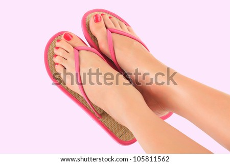 female legs in pink sandals on pink background - stock photo