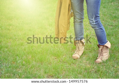 Female legs in shoes for hiking standing on a grass, in jeans with jacket in sunlight - stock photo
