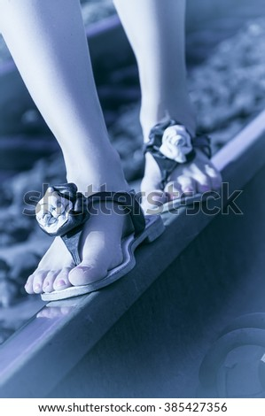 Female legs in summer sandals on the rails - stock photo