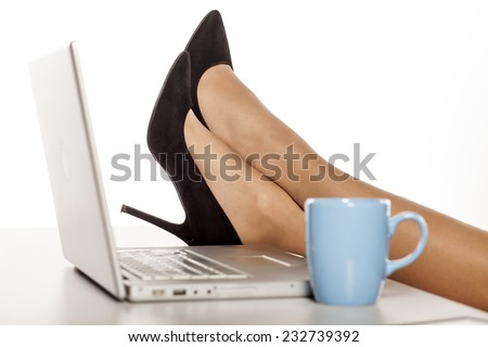 female legs in the high heels, on a table with a laptop - stock photo