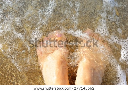 Female legs in the waves of the surf - stock photo