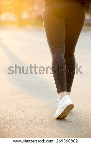 Female legs in white sneakers running on concrete, jogger practicing, close-up. Healthy, active lifestyle concepts, copy space - stock photo