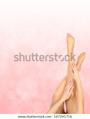 female legs massage with hands over pink bokeh background - spa and beauty concept - stock photo