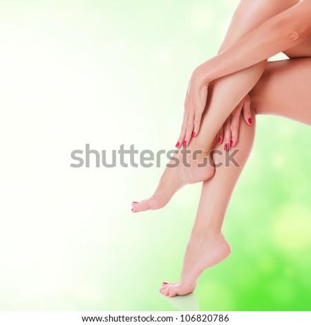 Female legs on green blurred background - stock photo
