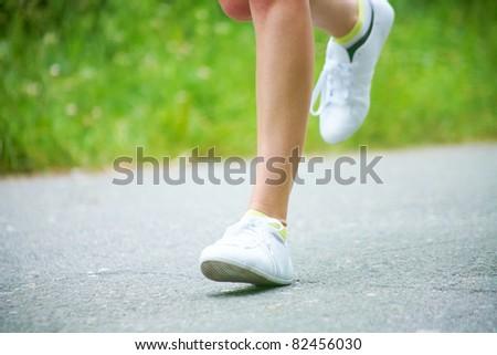 Female legs running on the road - stock photo