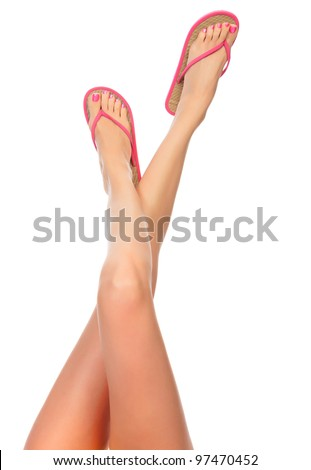 Female legs with pink flip-flops, isolated on white background.