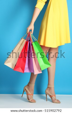 Female legs with shopping bags on a blue background. The concept of shopping, sale, discount.
