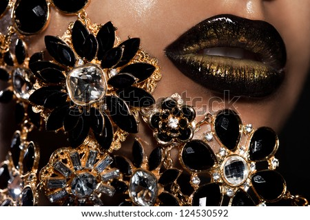 female lips with golden jewelry - stock photo