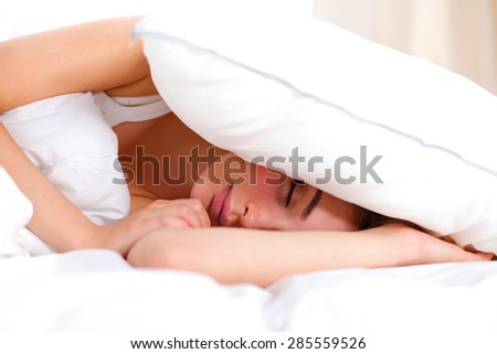 Female lying on bed and closing her ears with pillow. - stock photo