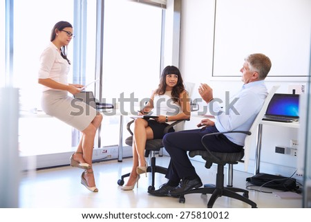 Female manager talking to colleagues in a modern office - stock photo