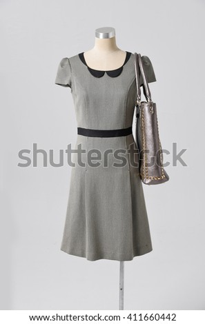 female mannequin in sundress with bag on gray background