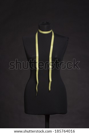 Female mannequin with a tape measure on black background. - stock photo