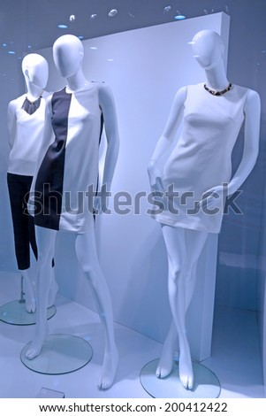 Female mannequins in blue light in the window of a fashion store.                                - stock photo