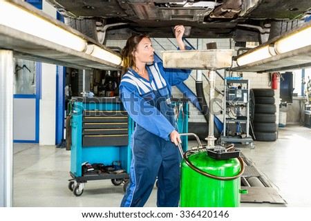 Female mechanic repairing car on hydraulic lift in automobile shop - stock photo