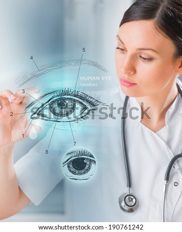 Female medical doctor working with virtual interface examining human eye - stock photo