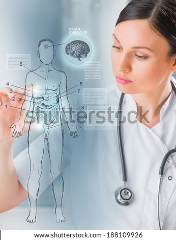Female medical doctor working with virtual interface examining human male body - stock photo
