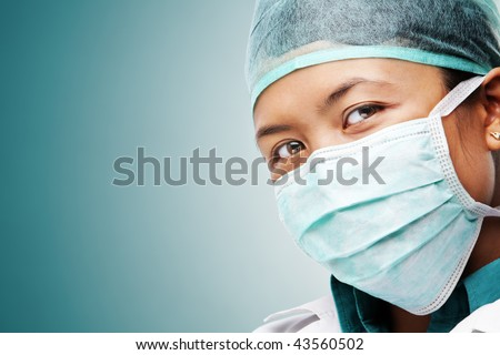 Female medical worker gazing to camera with all her protective wears - stock photo