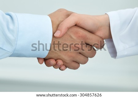 Female medicine doctor shaking hands with male patient. Partnership, trust and medical ethics concept. Handshake with satisfied client. Healthcare and medical concept - stock photo