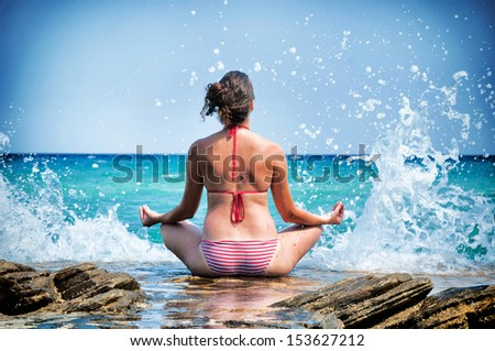 Female meditate on the seaside with big waves. Selective focus on the female - stock photo