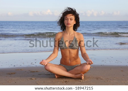 Female meditating on the beach - stock photo