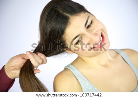 Female model getting long hair pulled painful expression