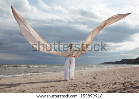 female model in extreme long beige dress posing dynamic in the beach. waving fabric. fluttering long skirt like a wings - stock photo