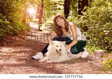 Female model in forest with Samoyed dog - stock photo