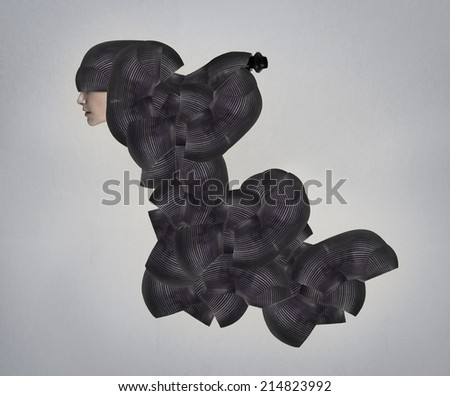 Female model profile in a black bizarre and surreal headgear and a sort of dress - stock photo