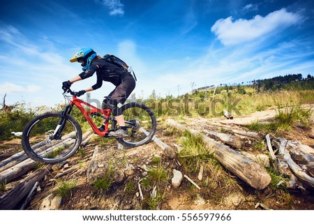 Female Mountain Bike cyclist riding track at sunny day in European mountains
