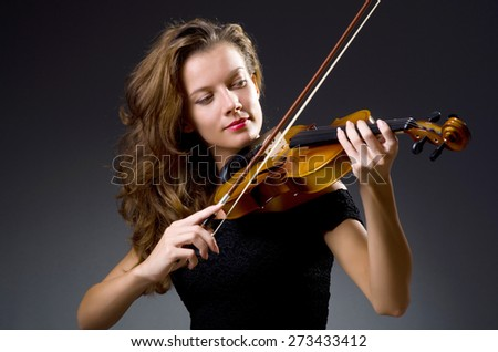 Female musical player against dark background - stock photo