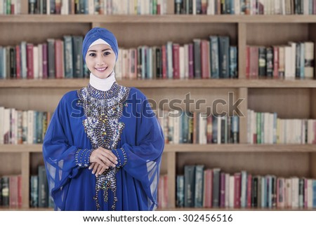 Female muslim student wearing blue dress, shot in library - stock photo