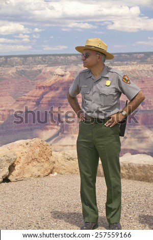 Female National Park ranger looking at South Rim of Grand Canyon National Park in mid-summer in Arizona - stock photo