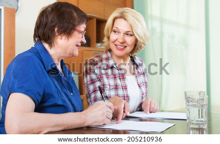 Female notary helping mature client drawing up of will - stock photo